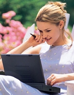 A pretty woman wearing stud earrings and working on a laptop