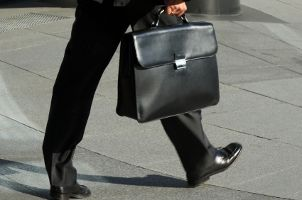 Man wearing dress shoes and carrying a briefcase