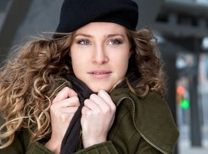 Woman in a green winter coat and black beanie