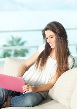 Girl on a couch with a pink netbook