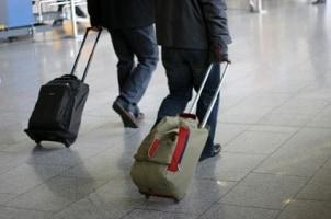 Travelers toting stylish wheeled backpacks