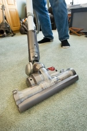 A man uses his trusty vacuum to clean the carpet