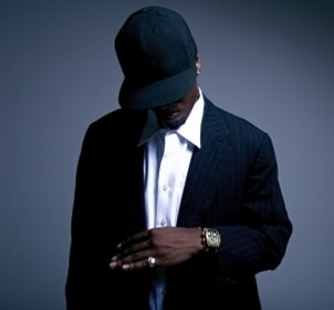 A sexy black man wearing a luxury Concord watch, a gold ring, a black baseball cap and a suit