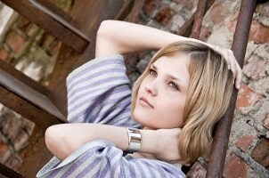 Pretty blond girl on an urban fire escape wearing a Citizen watch and a striped sweater