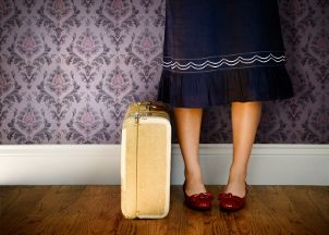 Woman wearing a navy blue skirt standing by suitcase