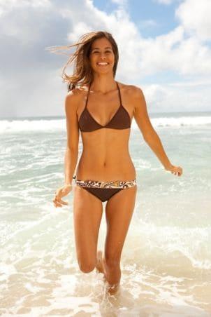 Woman running in the ocean in flattering women's swimwear