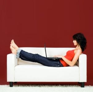 Woman wearing jeans and sitting on a couch