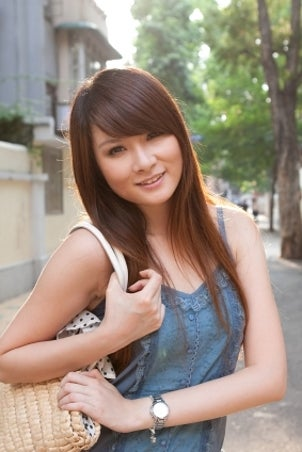 Pretty Asian student wearing a silver watch and a denim dress outside