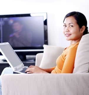 Woman typing on a netbook at home