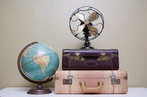 Retro fan on old-fashioned suitcases next to globe