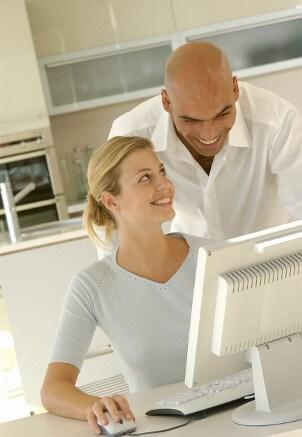 Couple looking at a desktop computer screen