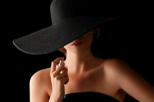 A woman in a hat putting on perfume