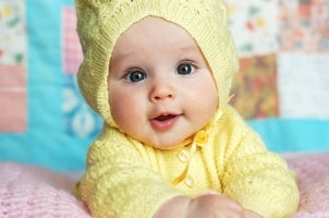 Baby girl in yellow sweater lying on a baby quilt