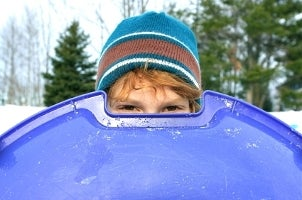 Little boy peering over his sled