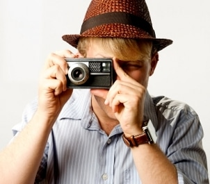 Cute retro guy taking a picture while wearing a Hamilton watch and an orange hat