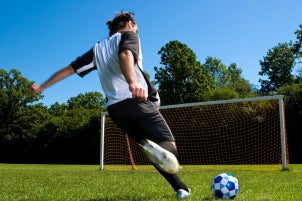 Athlete kicking a soccer ball into the net on a soccer field