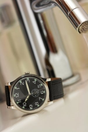 A black luxury watch sitting on a white and silver sink