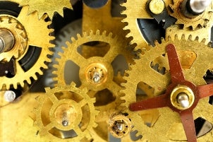 The bright gold gears of a mechanical watch movement