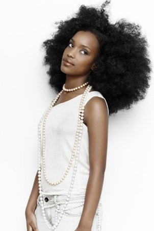 A cool girl wearing white jeans, a white top and a long strand of pearls