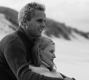 Couple wearing sweaters on the beach