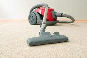 Red canister vacuum on beige carpet