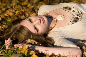 A pretty girl with auburn hair lying in a field and wearing a sweater and a floral pendant