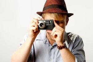 Man in a hat holding a camera