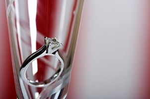 A princess-cut diamond engagement ring in a champagne flute