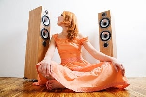 Red-haired woman listening to large stereo speakers