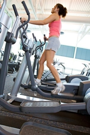Woman working out on an elliptical trainer at the gym