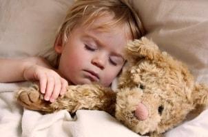 Boy with a teddy bear in a convertible crib