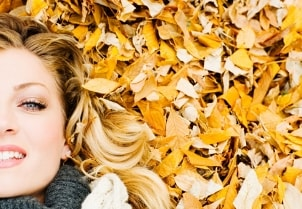 Woman with natural cosmetics laying on fall leaves