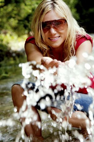 Woman in sunglasses playing in water