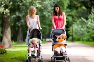 Two mothers on a walk with babies in strollers