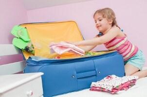 Little girl packs blue kids' luggage