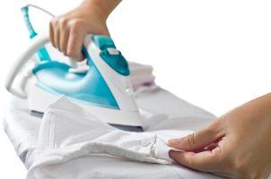Woman irons dress shirt with a steam iron