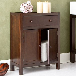 Wooden bathroom cabinet with candles and tp