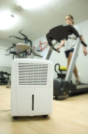 Dehumidifier cools gym while woman runs on treadmill