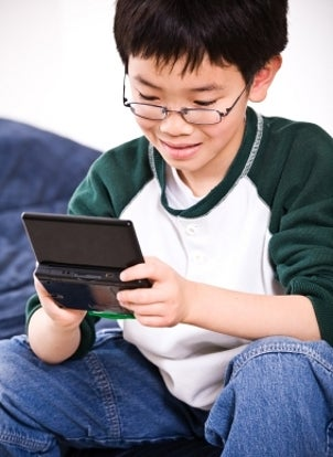 Young boy playing Nintendo DS games on a handheld