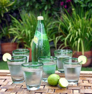 Green-rimmed glasses filled with sparkling water and garnished with limes