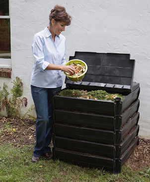 Large black composter in a backyard