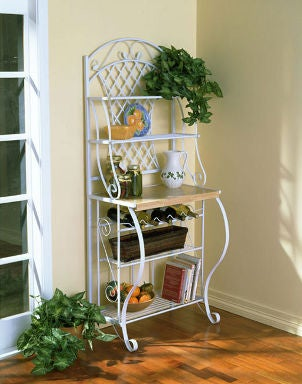 White kitchen rack holds cookbooks, fruit and dishes