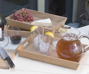 Wooden serving trays hold iced tea, grapes and cheese