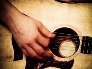 Man strumming an acoustic guitar