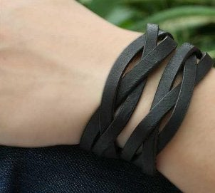 A woman's slender wrist with a cool black braided leather bracelet