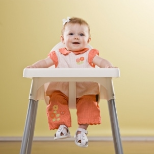 Cute baby girl sitting in a high chair