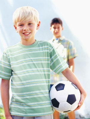 Two boys wearing summer clothes, ready to play soccer