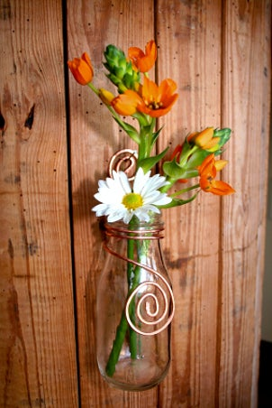 A lovely rustic vase made from a canning jar holding orange tulips and white daisies