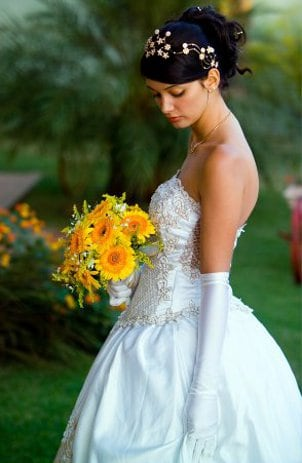 Bride holding a bright orange and yellow bouguet of fresh flowers