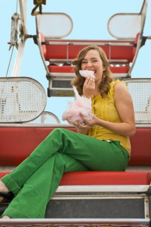 Young woman eating cotton candy on a ferris wheel